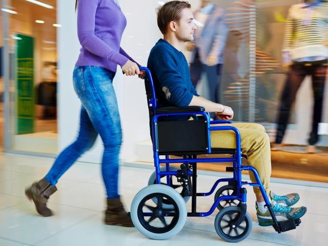 Physically impaired man in wheelchair doing shopping with his girlfriend in mall